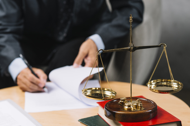legal-adviser-signing-contract-with-justice-scale-foreground_23-2147898662